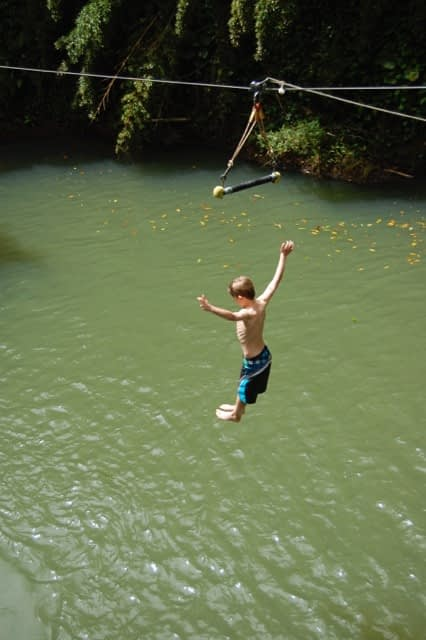 boy jumping into lagoon